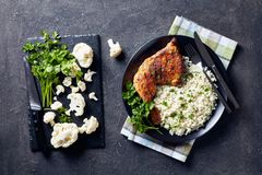 Broiled chicken leg quarter with Cauliflower rice. Broiled chicken leg quarter served with Cauliflower rice or couscous  served on a black plate on a concrete royalty free stock photos