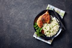 Broiled chicken leg quarter with Cauliflower rice. Broiled chicken leg quarter served with Cauliflower rice or couscous  served on a black plate on a concrete stock photos