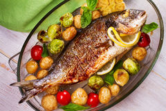 Broiled dorado fish with brussels sprouts, tomatoes, garlic, young potato and greens. Roasted dorado fish with brussels sprouts, tomatoes, garlic, young potato stock images