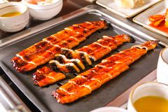 Broiled eels on table in restaurant stock photography