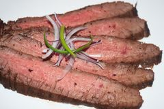 Broiled Flank Steak Slices. With scallions and onions on a white background ready to be served stock photography