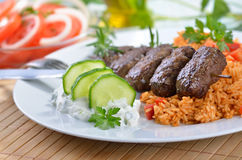 Broiled meat balls. Greek meat balls with paprika rice and tsatsiki, in the background tomato salad with onion rings royalty free stock photos