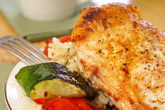 Broiled Pepper Chicken. Broiled chicken breast with cayenne and cracked black pepper, served with zucchini, red bell peppers, and wild brown rice stock image
