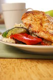 Broiled Pepper Chicken. Broiled chicken breast with cayenne and cracked black pepper, served with zucchini, red bell peppers, and wild brown rice royalty free stock photo