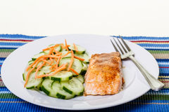 Broiled Salmon with Cucumbers and Carrots. A dinner of baked salmon with sliced cucumbers and shredded carrots royalty free stock photo