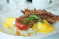 Broiled Tomato on Breakfast Plate. Eggs Benedict with hash browns, broiled tomato, asparagus and bacon stock photos