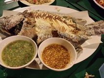 Broiled whole fish. Broiled fish on a plate with tasty side dishes. Malaysian food Stock Photos