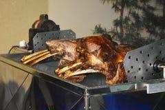 Brok van rundvleesrib op de rol wordt geroosterd die Vleesbarbecue voor vele mensen Geroosterd rundvlees Lapje vlees op het been stock afbeelding