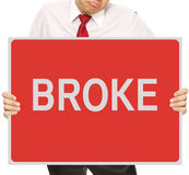 Broke. A sad businessman holding a signboard indicating Broke Stock Photo