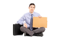 Broke businessman begging with a piece of cardboard Royalty Free Stock Photography