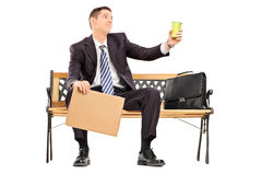 Broke businessman holding a cup and blank banner Royalty Free Stock Image