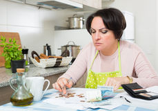 Broke housewife without money enough for payment. Miserable housewife sitting with bills and money in kitchen Stock Photos