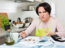 Broke housewife without money enough for payment. Miserable housewife sitting with bills and money in kitchen Royalty Free Stock Photo