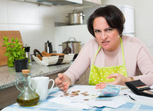 Broke housewife without money enough for payment. Miserable housewife sitting with bills and money in kitchen Stock Photo