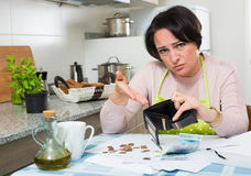 Broke housewife without money enough for payment. Miserable housewife sitting with bills and money in kitchen Stock Photography