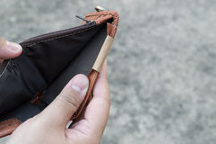 Broke man showing his brown leather wallet with no money stock photo