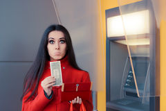 Broke Woman Holding One Dollar in Front of an ATM Royalty Free Stock Images