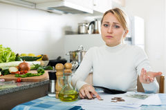 Broke woman with money and bills in kitchen Royalty Free Stock Photos