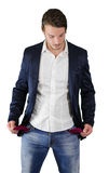 Broke young man looking at empty pockets Royalty Free Stock Photos