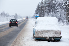 Broken abandoned car covered with snow and ice is on roadside at winter Royalty Free Stock Images