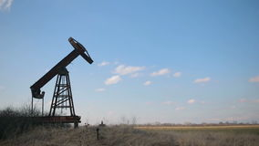 Broken and abandoned oil pump on a background of blue sky and white clouds. stock footage