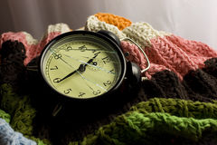 Broken alarm clock time. A detail of a broken alarm clock lying in colorful blankets Royalty Free Stock Photos