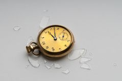 Broken Antique Pocket Watch. A broken antique gold watch laying on the floor surrounded by shattered glass from the watch crystal Royalty Free Stock Photos