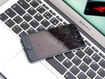 Broken Apple iPhone On Apple MacBook Air Laptop. Los Angeles, CA, USA - December 07, 2015: Broken Apple iPhone with cracked screen on Apple MacBook Air laptop Stock Photos