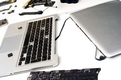 Broken Apple MacBook iPad. Broken components of an apple macbook ipad computer on a white background with a copyspace area for computer repair design ideas royalty free stock photography