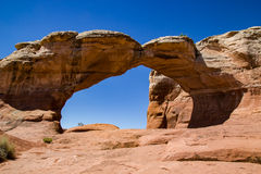 Broken Arch. Rock formations and  blue sky in Arches National Park, Utah. This natural bridge is called Broken Arch for the crack in the center of the arch Stock Image