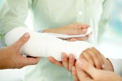 Broken arm. Close-up of broken arm in plaster cast Stock Images