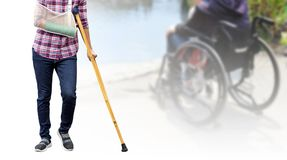 Broken arm, injury woman standing wearing shirt and jeans with a. Rm splint and holding wooden crutches isolated on blurred background patient sitting on royalty free stock image