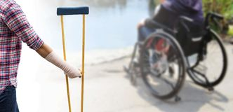 Broken arm, injury woman standing wearing shirt and jeans with a. Rm splint and holding wooden crutches on blurred background patient sitting on wheelchair royalty free stock image