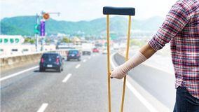 Broken arm, injury woman standing wearing shirt and jeans with a. Rm splint and holding wooden crutches isolated on Japanese highway with mountain background stock image