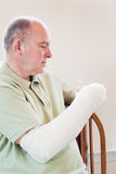 Broken Arm. Man with broken arm.  Natural light. Selective focus is on the cast Stock Image