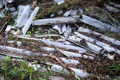 Broken asbestos cement sheets in nature, toxic waste