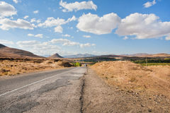 Broken asphalt road in the dry grass valley of the Middle East under white clouds. And mountain range in the distance Royalty Free Stock Images