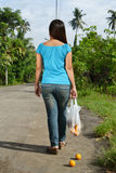 Broken Bag!. A young lady walking in the street with a broken shopping bag stock photography