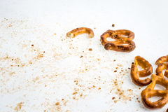 A broken baked pretzels on white. A couple of broken baked pretzels on white with salt stock photography
