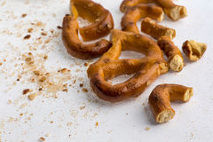 A broken baked pretzels on white. A couple of broken baked pretzels on white with salt royalty free stock images