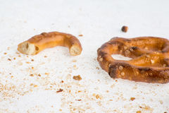 A broken baked pretzels on white. A couple of broken baked pretzels on white with salt royalty free stock photography