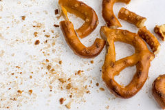 A broken baked pretzels on white. A couple of broken baked pretzels on white with salt stock image