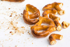 A broken baked pretzels on white. A couple of broken baked pretzels on white with salt royalty free stock photos