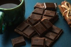 Broken bar of chocolate, cinnamon and cup of coffee an black table, close up.  Stock Image