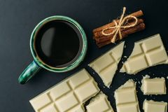 Broken bar of white chocolate, cinnamon and cup of coffee an black table, top view.  Royalty Free Stock Image