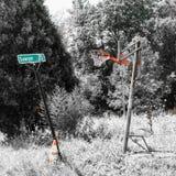 Broken basketball hoop and street sign in overgrown field stock images