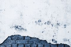 Broken battered wall with stucco and bricks in classic blue. Beautiful tinted color 2020. Grunge background