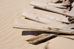 Broken beach defences. With fence pieces lying in the sand Stock Image