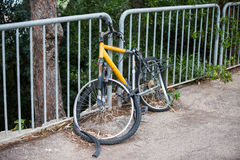 Broken bike attached to a street fence Stock Photos