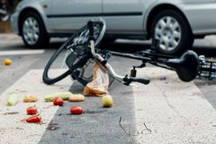 Broken bike and fruits on pedestrian lines after traffic incident with a car. Broken bike and vegetables on pedestrian crossing after a traffic incident with a stock photos